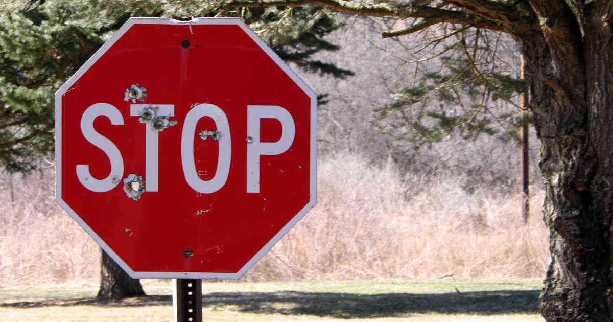 Segnale stradale dello Stop crivellato di colpi