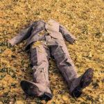 Uomo steso sopra un tappeto di foglie