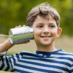 Bambino che ascolta un telefono fatto con un barattolo e lo spago