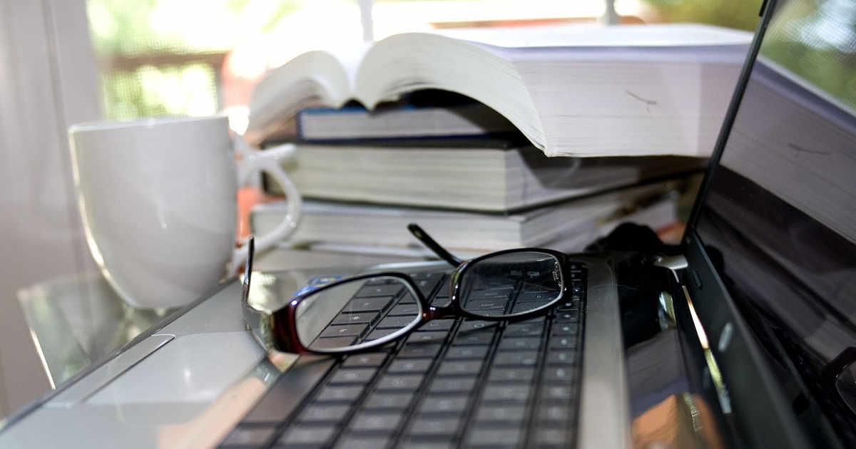Occhiali sopra la tastiera e libri