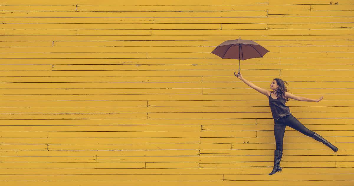 Ragazza che vola appesa a un ombrello