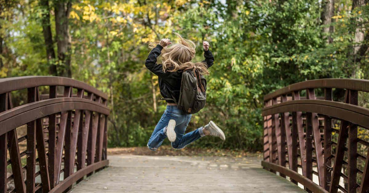 Bambina che salta felice sopra a un ponte