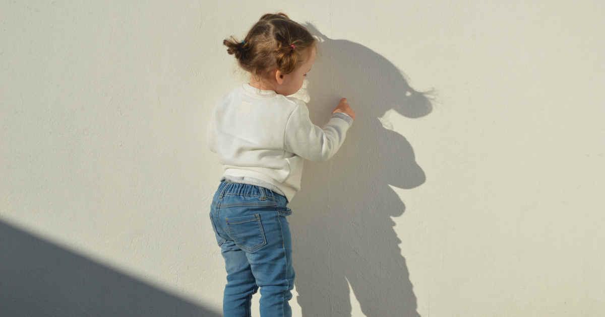 Bambina che fa esperienza con la sua ombra