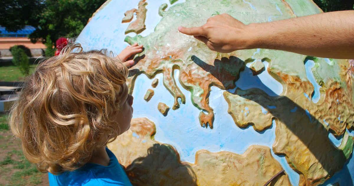 Bambino che impara a conoscere il mappamondo