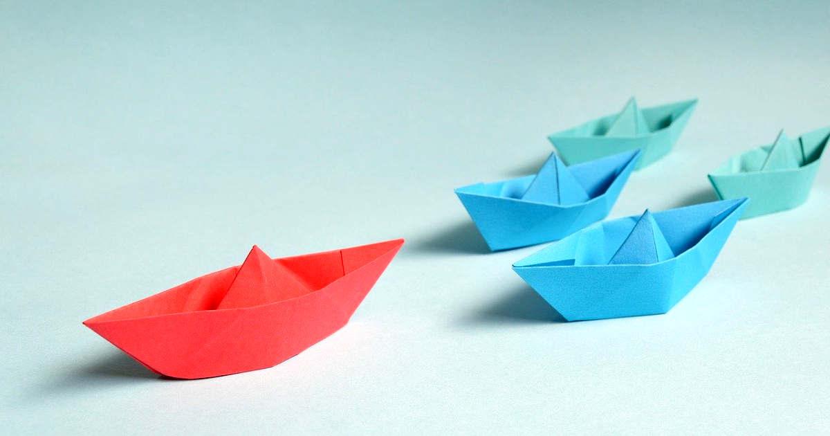 Una barca rossa di carta, il leader, che guida altre barche di carta colorata
